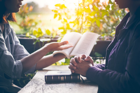 Asian girls are reading the sacred scriptures by pointing to the text of the book. And share the gospel and to explain the meaning of the Bible to her friend understand. Amid the meadows and greenery