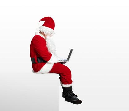 santa claus watching laptop and sitting on blank panel