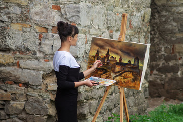 The female artist paints a picture of the castle.