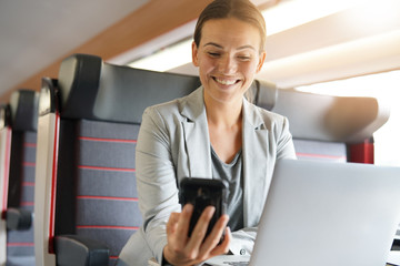 Businesswoman smiling at cellphone on train