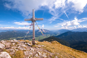 Beautiful mountain panorama with blue sky and clouds, in foreground the cross of top.