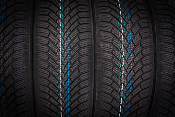 Winter car tires in row isolated on black