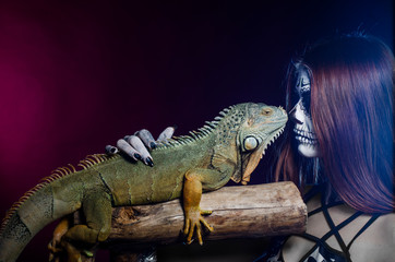 dead face girl and green iguana. Halloween.