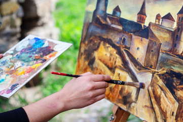 The female artist paints a picture of an ancient fortress