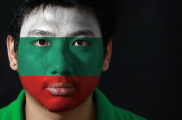 Portrait of a man with the flag of the Bulgaria painted on his face on black background, white green and red color.