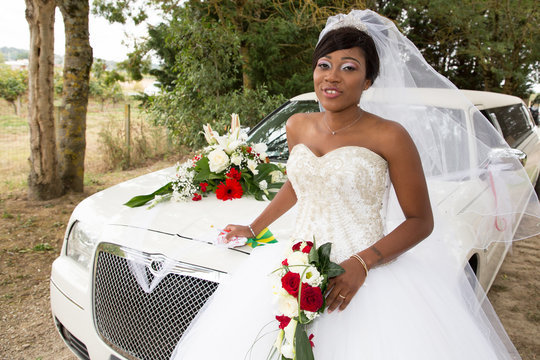 pretty young african american black bride posing with white limousine car in wedding day
