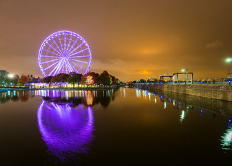 A brightly lit ferris wheel in the old port area of Montreal, Canada. Beautifully reflected in the water Wall mural