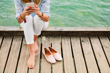 Girl on a wooden pier using smartphone.