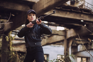 airsoft woman soldier with a rifle playing strikeball In old building