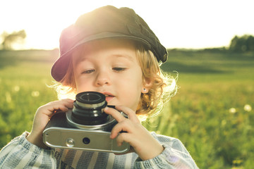 Portrait of a little girl taking pictures with a camera.Concept of children playing