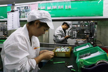 Employees work at a production line of lithium ion batteries inside a factory in Dongguan