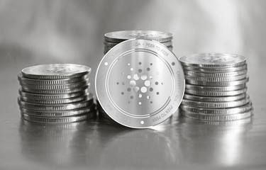 Cardano (ADA) digital crypto currency. Stack of silver coins. Cyber money.