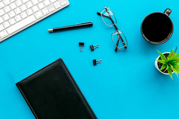 Office desk of creative person or hipster.Cute workplace. Keyboard and glasses near coffee, notebook, green room plant and stationery on blue, turquoise background top view copy space