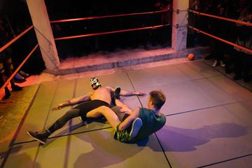 Fighting men on wrestling ring