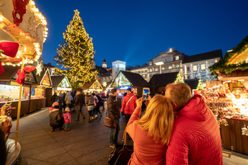 Tourists enjoying Graz Christmas market and taking pictures at the Christmas tree