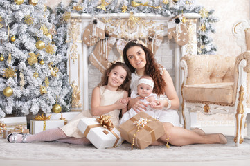 Portrait of happy mother with cute little daughters posing