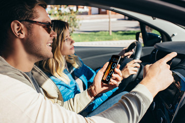 man with smartphone showing direction to wife  in car