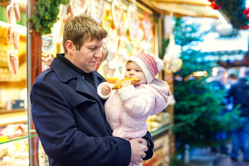 Middle aged father holding baby daughter girl near sweet stand with gingerbread and nuts.