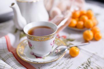 Decorative orange mandarins, tangerines, cup of tea, home mandarins, small mandarines.