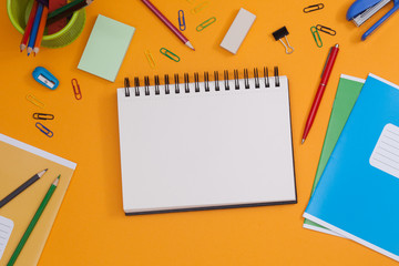 Empty spiral notebook with white page and multicolored stationery on a orange table. Workplace with notepad on colored background. Sketch-book for input the text, top view. Back to school concept.