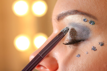 Woman applying mascara on her eyes by brush