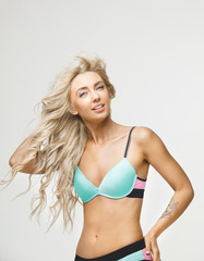 beautiful woman with blond hair wears bright bathing suit on white isolated background. Pretty girl posing in bikini at studio.