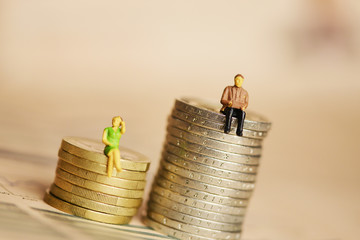 Income inequality by gender with human miniature silhouettes on pile of coins