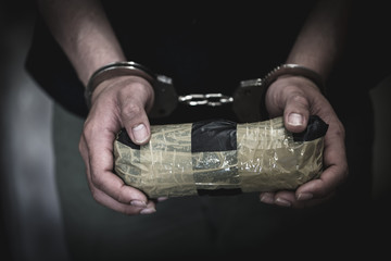 Drug traffickers were arrested along with their heroin. Police arrest drug trafficker with handcuffs. Law and police concept,26 June, International Day Against Drug Abuse and Illicit Trafficking