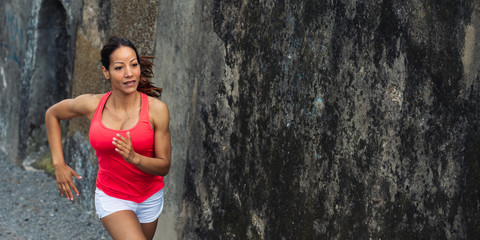 Female fit hispanic athlete running against concrete wall in background for copy space. Sporty fitness cheerful woman training.