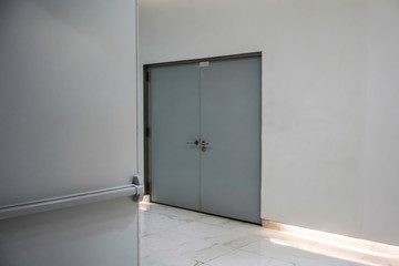 metal grey doors on white wall and walking light.