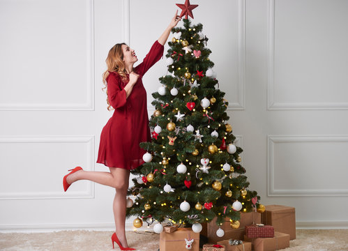 Cheerful woman decorating the christmas tree