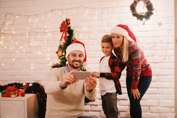 Father taking picture of him and his family. In background Christmas decoration. Christmas holidays concept.