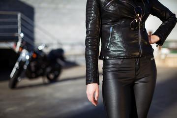 Biker woman in leather jacket standing in front of motorbike