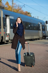 Busy young woman in coat with suitcase talking on the phone at the train station