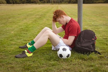 Football player relaxing in the field