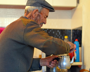 Senior man is making tea in the kitchen.  old turkish man brew the turkish tea.