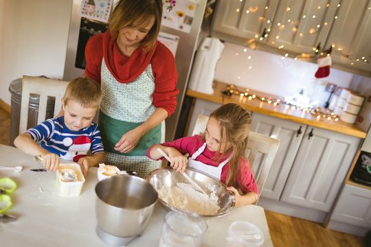 Mother and kids preparing dough for Christmas cookies