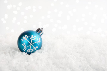 Blue Christmas ball on the snow with shiny background.