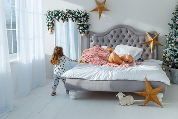 Family spending free time at home. Cheerful family having fun with their daughter on the bed. On the eve of Christmas and New Year