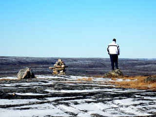 Lonely man on the top of a mountain in Kuujjuaq, standing by an inuksuk in Kuujjuaq