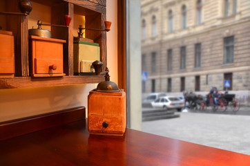 Coffee grinder on a table in a cafe near the window.