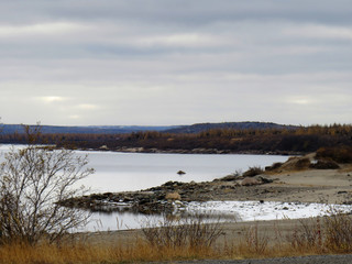 waterscape with mountains surrounding it showing a frozen beach in Kuujjuaq