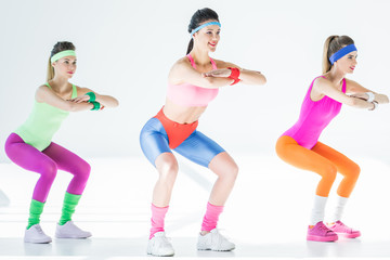full length view of sporty smiling girls doing squat on grey