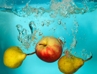 Pears and apple splash of water on blue bckground
