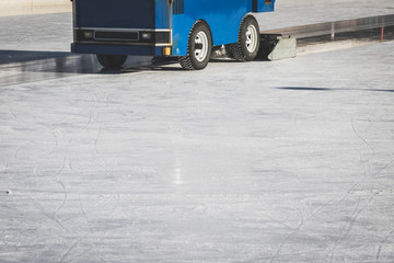 Machine polishing ice for outdoor skating on sunny winter day