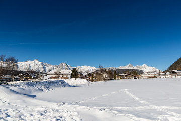 Seefeld village view over snowy field on sunny winter day