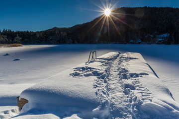snow covered pier with traces on lake Seefeld on sunny winter day