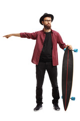 Male hipster holding a longboard and pointing in one direction