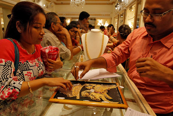 A salesman shows gold necklaces to a customer at a jewellery showroom during Dhanteras, a Hindu festival associated with Lakshmi, the goddess of wealth, in Kolkata