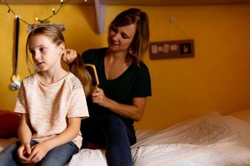 Mother combing daughters hair on bed